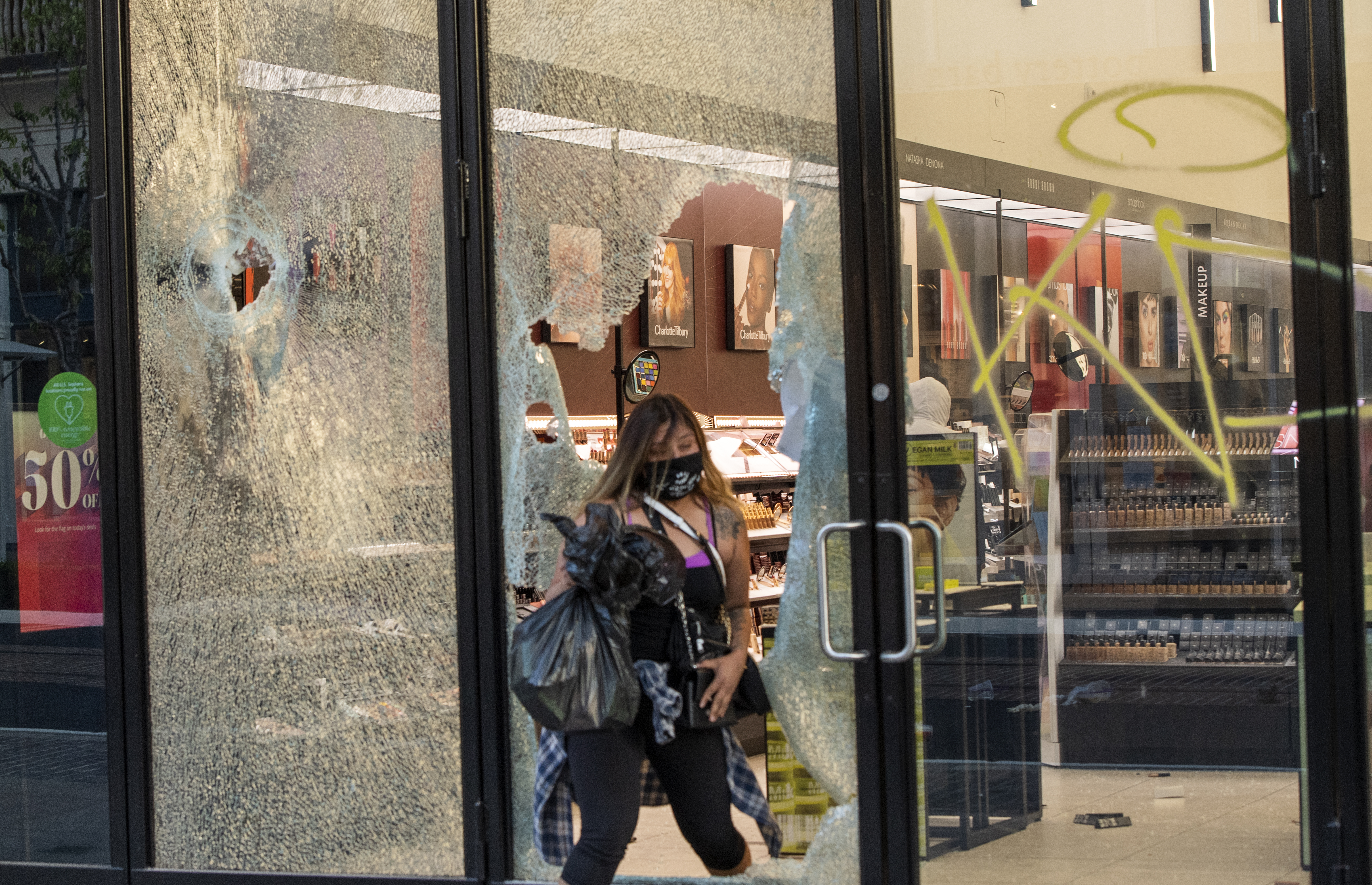 Mensen vernielen winkels en stelen.